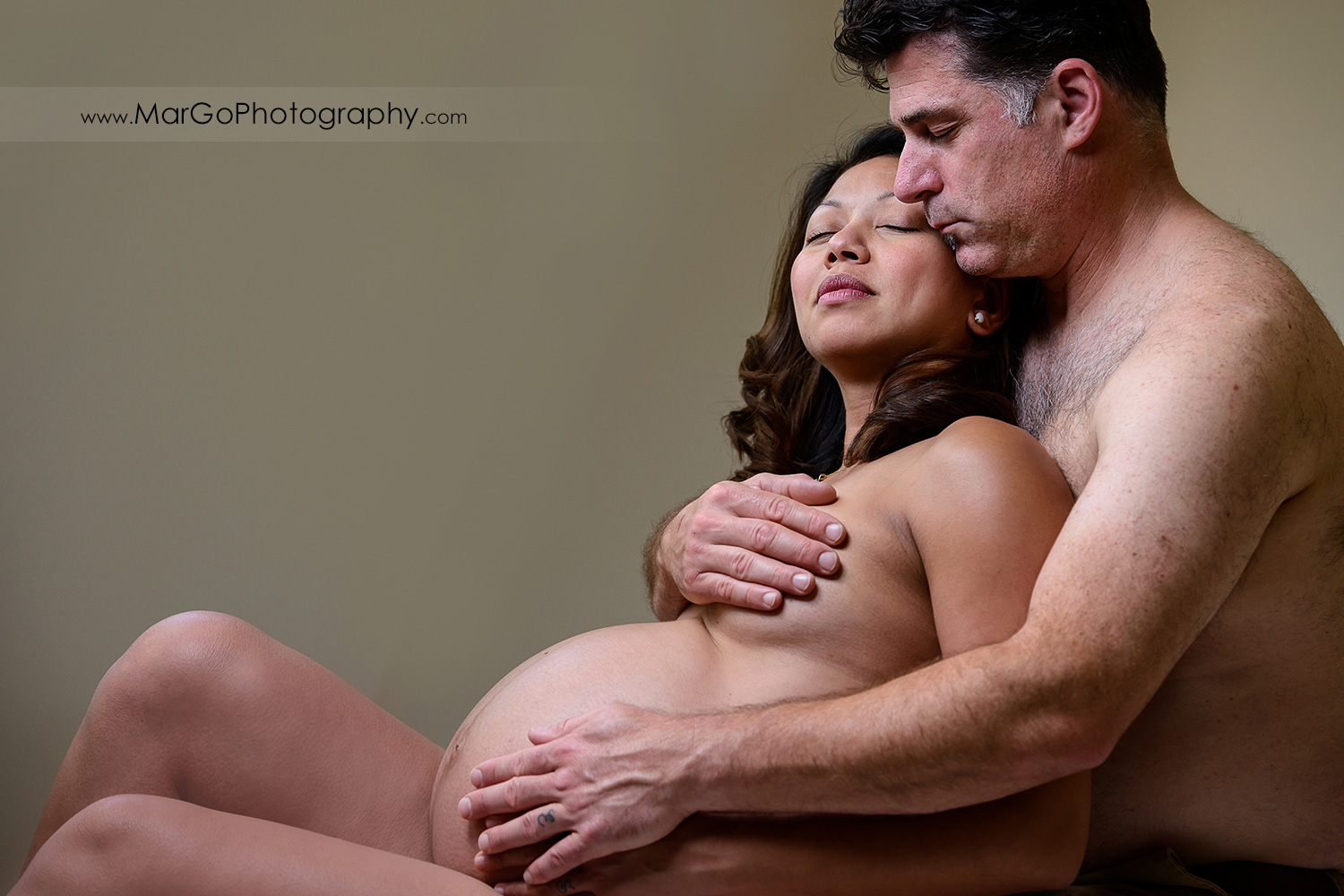 naked man sitting behind naked pregnant woman