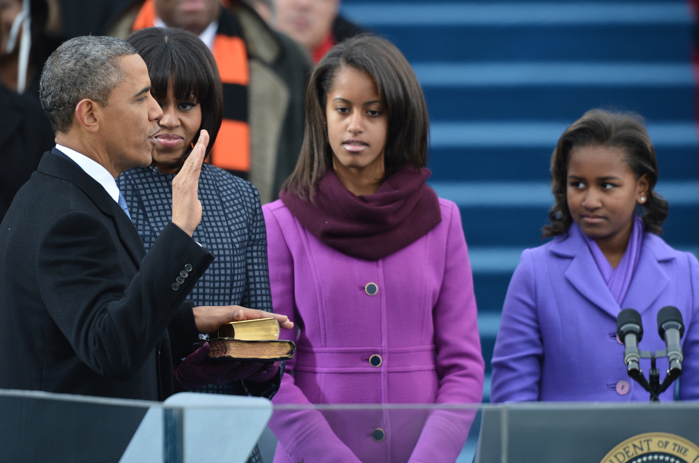 Description of . US President Barack Obama takes the oath of office in front of (L-R) First Lady Michelle Obama, daughters Malia and Sasha during the 57th Presidential Inauguration ceremonial swearing-in at the US Capitol on January 21, 2013 in Washington, DC. US Chief Justice John Roberts administered the oath.   JEWEL SAMAD/AFP/Getty Images