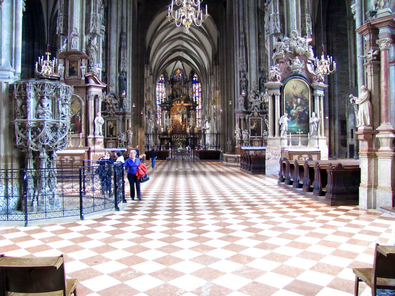 17-Nave (center aisle). On the left behind the railing is the stone pulpit—a masterwork of late gothic sculpture. So that the local language sermon could be better heard by worshipers in the days before microphones, the pulpit stands against a pillar out in the nave, instead of in the chancel at the front of the church.