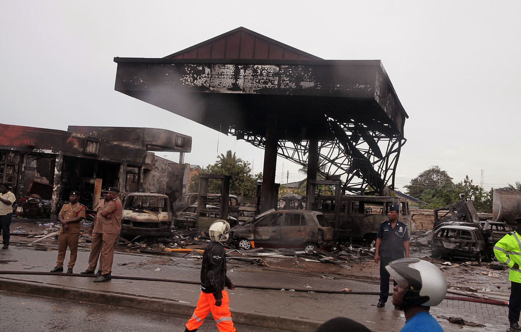 . Ghana security personnel stand near the gas station that exploded  in Accra, Ghana, Thursday, June 4, 2015. Flooding in Ghana\'s capital swept stored fuel into a nearby fire, setting off a huge explosion at a gas station that killed scores of people and set alight neighboring buildings, authorities said Thursday. (AP Photo/Christian Thompson)