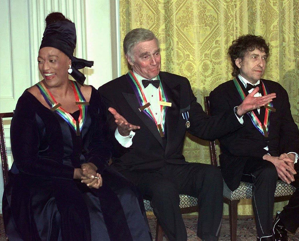 . 1997: Kennedy Center Honoree Charlton Heston, center, acknowledges the applause of the audience flanked by singer/songwriter Bob Dylan at right, and soprano Jessye Norman at a gala reception in the East Room of the White House hosted by President and Mrs. Clinton  Sunday evening, Dec. 7, 1997.   (AP Photo/J. Scott Applewhite)