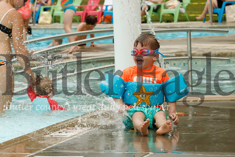 Owen White, 3, of Zelienople splashes around in the kiddie pool fountains at Zelienople Community Pool Monday. Seb Foltz/Butler Eagle