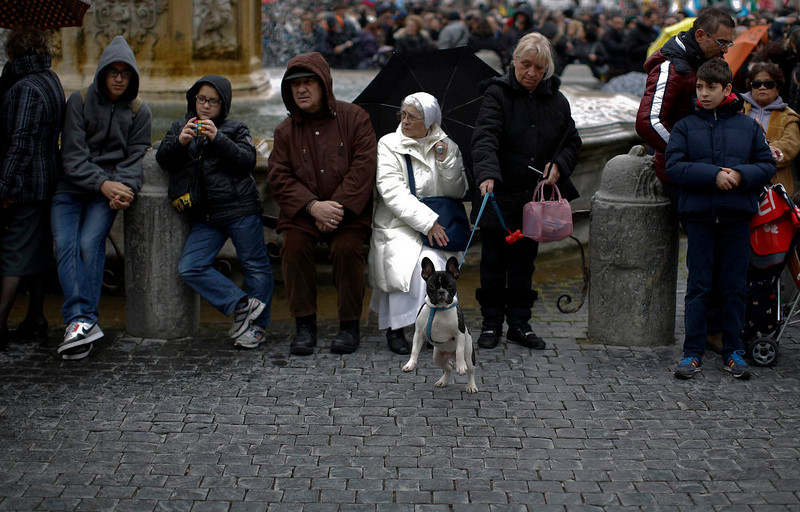 . Faithful rest while waiting for Pope Francis to appear at the window of his future private apartment to give the Sunday Angelus prayer at the Vatican March 17, 2013. Earlier, Pope Francis took on the role of a simple parish priest on Sunday, saying Mass for the Vatican\'s resident community and urging listeners to not to be so quick to condemn others for their failings. REUTERS/Paul Hanna