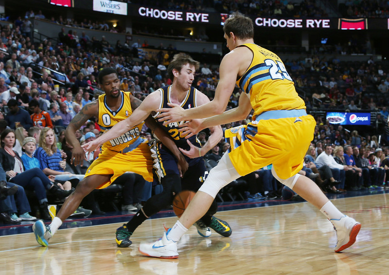 . Utah Jazz forward Gordon Hayward, center, loses control of the ball as Denver Nuggets guard Aaron Brooks, left, and center Timofey Mozgov, of Russia, cover in the first quarter of an NBA basketball game in Denver on Saturday, April 12, 2014. (AP Photo/David Zalubowski)