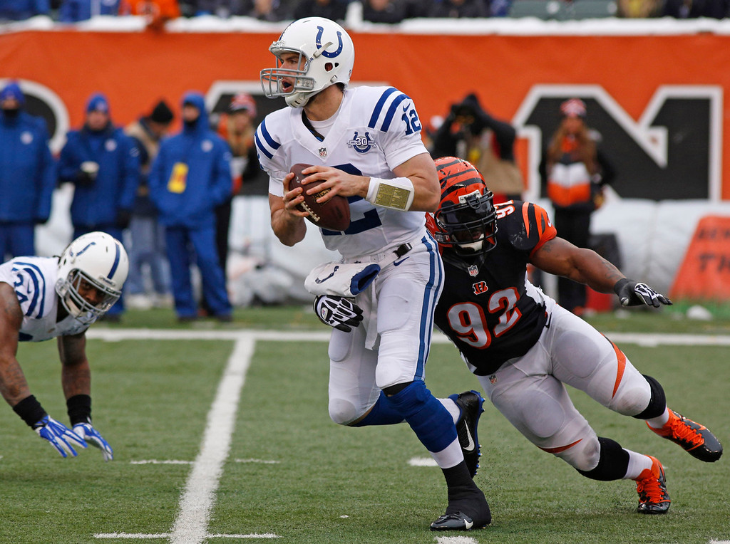 . Indianapolis Colts quarterback Andrew Luck (12) is pursued by Cincinnati Bengals outside linebacker James Harrison (92) in the first half of an NFL football game, Sunday, Dec. 8, 2013, in Cincinnati. (AP Photo/David Kohl)
