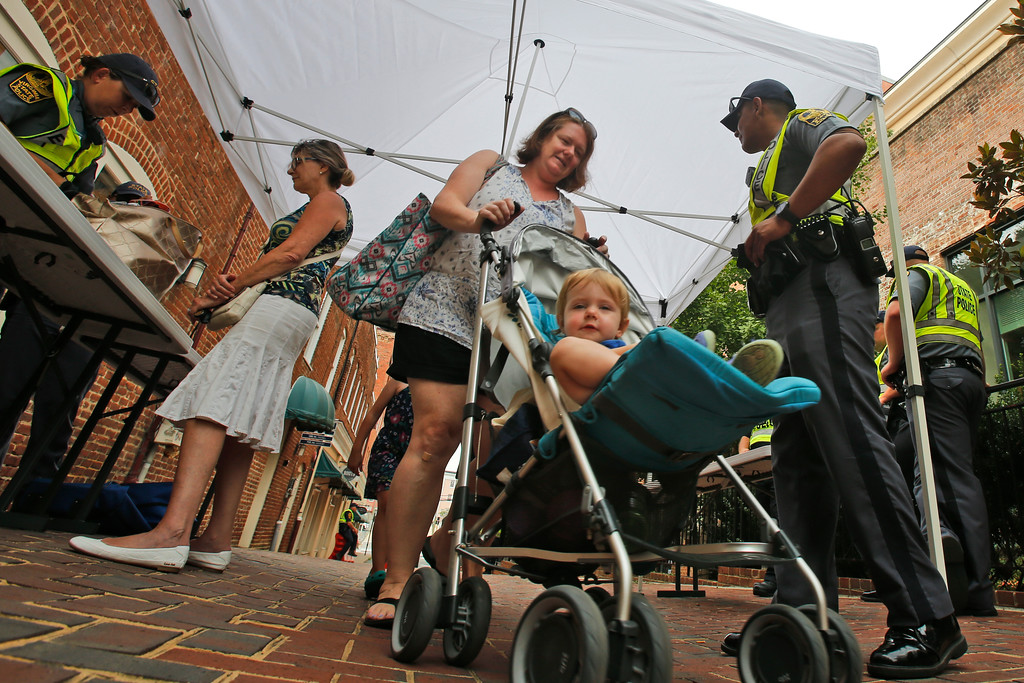 . Erica Bahnuk and her daughter Hazel, exit a check point as State Police inspect  bags to lock down the downtown area in anticipation of the anniversary of last year\'s Unite the Right rally in Charlottesville, Va., Saturday, Aug. 11, 2018. The Governor has declared a state of emergency in Charlottesville. (AP Photo/Steve Helber)