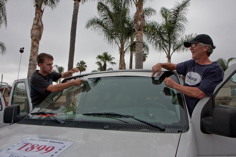 """Matt and Richard put the official """"Race Across America"""" window sticker on a van."""