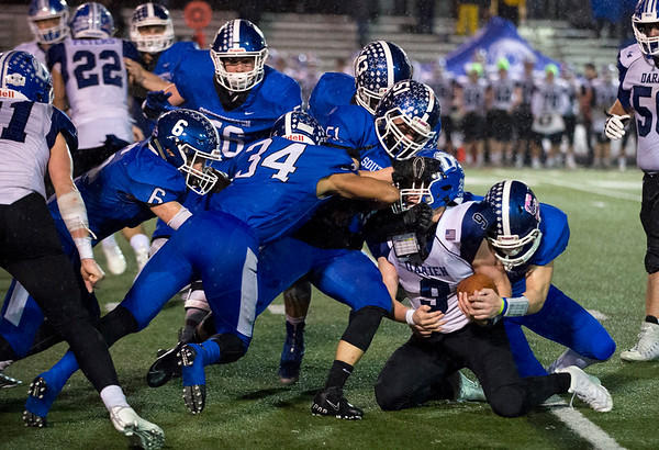 12/09/19 Wesley Bunnell | StaffrrSouthington football was defeated at home in a CIAC playoff game against Darien on a rainy Monday night December 9, 2019. Five Southing defenders swarm the Darien ball carrier.