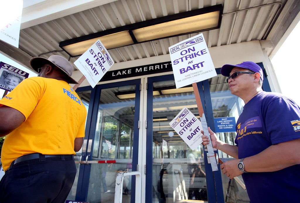 . BART employee Ben Lau, of Oakland, right, Tony Thurston of San Leandro, left, members of the Service Employees International Union Local 1021, picket with others in front of the Lake Merritt BART station in Oakland, Calif., on Wednesday, July 3, 2013. The BART strike is in its third day and bargaining talks will resume at 1 p.m. Wednesday. (Jane Tyska/Bay Area News Group)