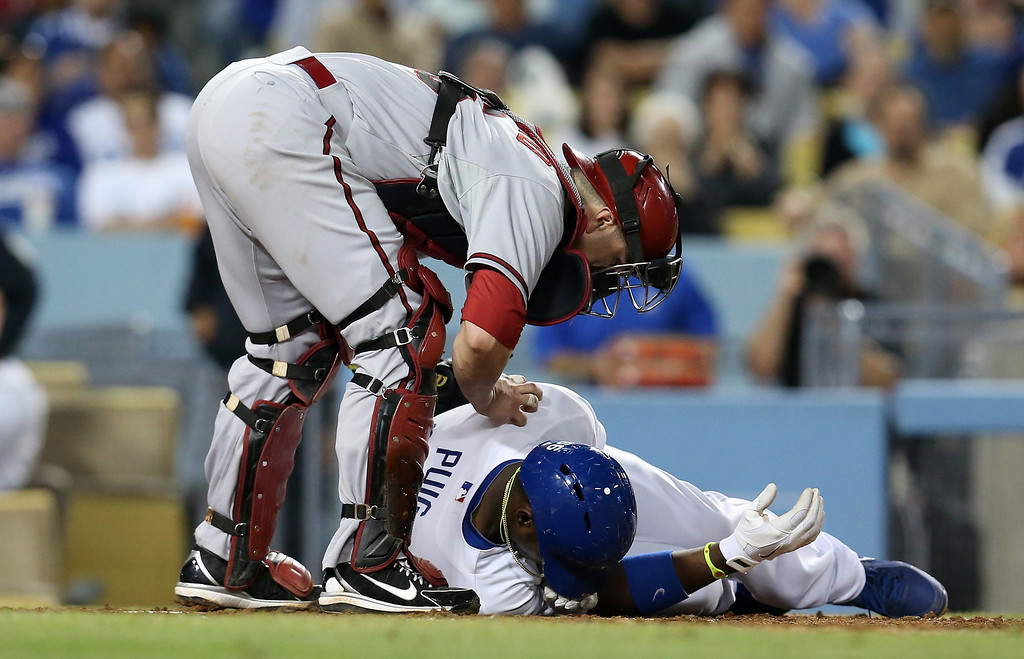 . LOS ANGELES, CA - JUNE 11: Catcher Miguel Montero #26 of the Arizona Diamondbacks bends over Yasiel Puig #66 of the Los Angeles Dodgers after Puig went down after being hit by a pitch in the sixth inning at Dodger Stadium on June 11, 2013 in Los Angeles,  (Photo by Stephen Dunn/Getty Images)