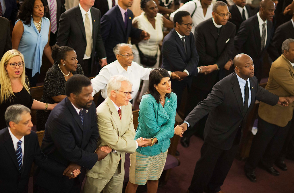 . South Carolina Gov. Nikki Haley, center right, joins hands with Charleston Mayor Joseph Riley, left, and Sen. Tim Scott, R-S.C., right, at a memorial service at Morris Brown AME Church for the people killed Wednesday during a prayer meeting inside the historic black church in Charleston, S.C., Thursday, June 18, 2015. Police arrested 21-year-old suspect Dylann Storm Roof Thursday in Shelby, N.C. without resistance. (AP Photo/David Goldman)