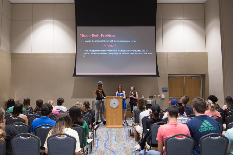 """Students give a presentation on """"Genes or Free Will."""" during the First Year Research Symposium."""