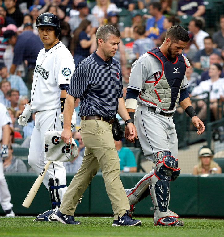 . Cleveland Indians catcher Yan Gomes, right, walks off the field with a trainer and leaves the game after he was hit by the baseball during an at-bat by Seattle Mariners\' Dae-Ho Lee, left, in the second inning of a baseball game, Tuesday, June 7, 2016, in Seattle. (AP Photo/Ted S. Warren)