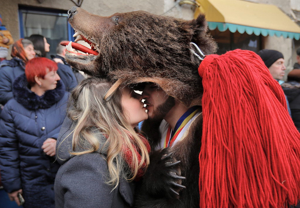 . In this Saturday, Dec. 30, 2017, picture a man wearing a bear fur costume kisses his girlfriend during an annual bear parade in Comanesti, Romania. (AP Photo/Vadim Ghirda)