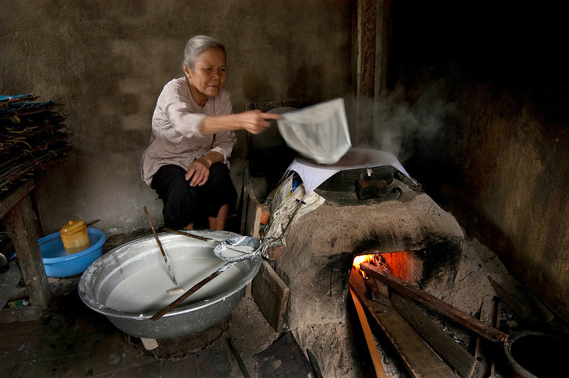 Woman making rise paper. She has been practicing her craft for decades and sitting in the same position for hours, But, her livelihood and family depended on these skills, which she had honed to a seemingly effortless precision. Such level of culinary craftsmanship comes only from  having done something tens of thousands of times.  Hoi An, Vietnam, 2008