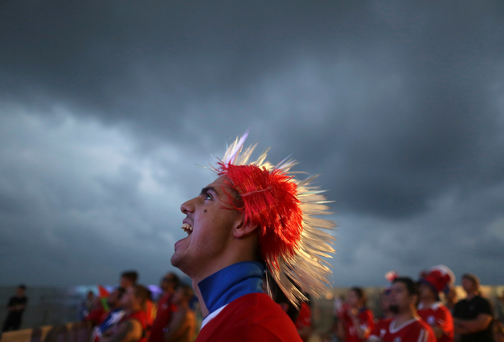 . A soccer fan wearing a Mohawk-styled wig in Chile\'s team colors, cheers as he watches a live broadcast of the group B World Cup match between Chile and Spain, inside the FIFA Fan Fest area on Copacabana beach, in Rio de Janeiro, Brazil, Wednesday, June 18, 2014. Chile defeated Spain, the defending champs, 2-0. (AP Photo/Leo Correa)