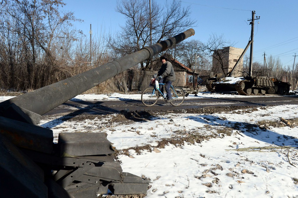 """. A man rides a bicycle past the wreckage of an Ukrainian army tank in Uglegorsk, 6 kms southwest of Debaltseve, on February 18, 2015. Ukrainian troops pulled out of the besieged flashpoint eastern town Debaltseve after it was stormed by pro-Russian rebels in what the EU said was a \""""clear violation\"""" of an internationally-backed truce. The retreat from Debaltseve -- a strategic railway hub sandwiched between the main rebel-held cities of Donetsk and Lugansk -- was a serious defeat for Ukrainian President Petro Poroshenko, who came to office vowing to crush the separatist uprising. VASILY MAXIMOV/AFP/Getty Images"""