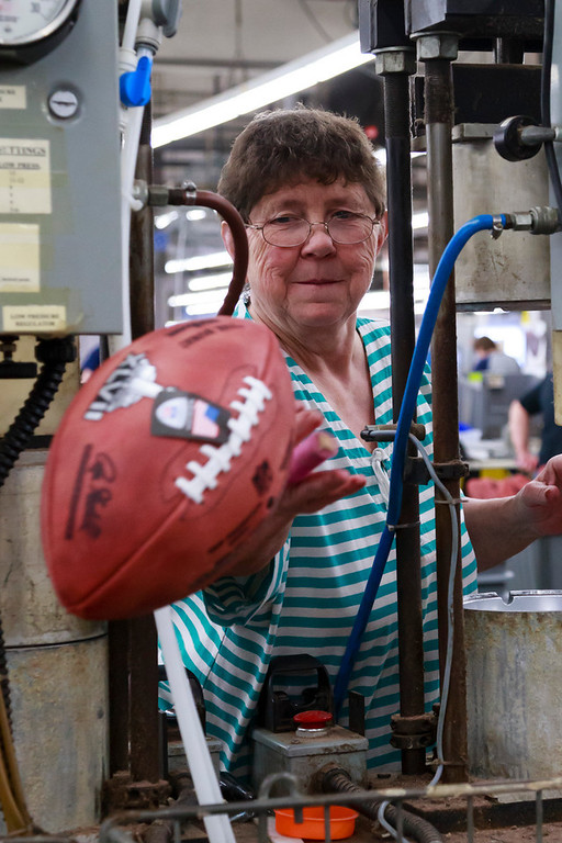 . Deb Conley tosses a finished official game ball for the NFL football Super Bowl XLVII into a bin to wait final inspection at Wilson Sporting Goods Co. in Ada, Ohio, Monday, Jan. 21, 2013.  (AP Photo/Rick Osentoski)