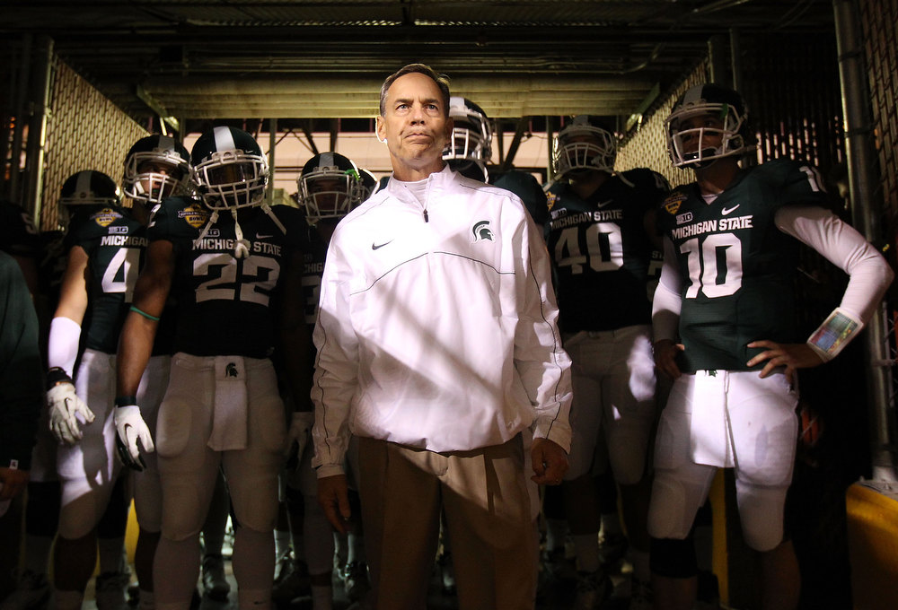 Description of . Head coach Mark Dantonio of the Michigan State Spartans stands with his team before taking the field for the Buffalo Wild Wings Bowl against the TCU Horned Frogs at Sun Devil Stadium on December 29, 2012 in Tempe, Arizona.  (Photo by Christian Petersen/Getty Images)