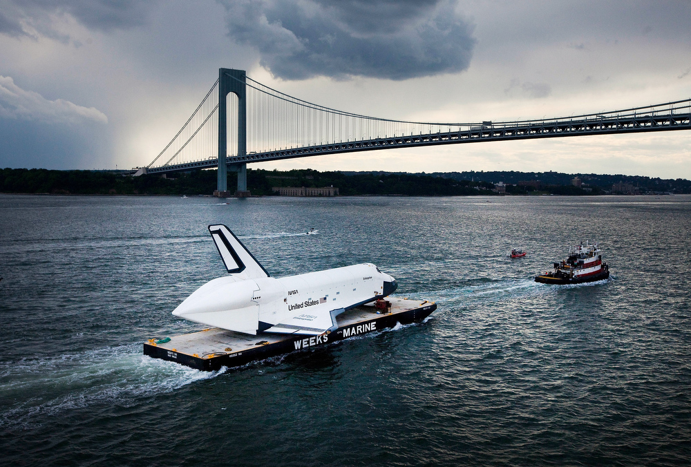 Description of . Space Shuttle Enterprise is carried by barge underneath the Verrazano-Narrows Bridge on June 3, 2012 in New York City.  Enterprise is on it's way to the Intrepid Sea, Air and Space Museum, where it will put on permanent display.  (Photo by Michael Nagle/Getty Images)