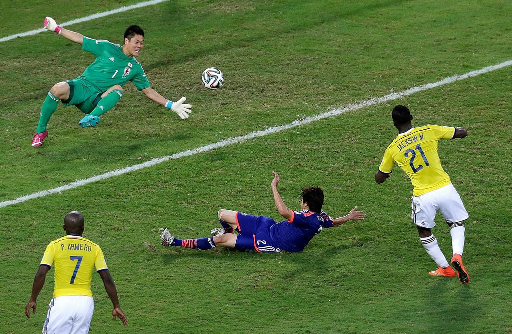 . Colombia forward Jackson Martinez, right, scores past Japan defender Atsuto Uchida and goalkeeper Eiji Kawashima during the second half of a group C World Cup soccer match at the Arena Pantanal in Cuiaba, Brazil, Tuesday, June 24, 2014. (AP Photo/Shuji Kajiyama)