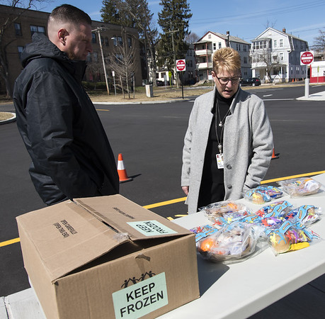 FILE Wesley Bunnell | Staff School lunches are being provided at no charge to New Britain residents in the wake of forced school closings due to the Coronavirus. Standing outside of Smalley School on Monday March 16, 2020 are Jeff Taddeo, Resident District manger for Whitsons School Nutrition, L, as he looks over the specially packaged cold lunches available along with CSDNB Superintendent of Schools Nancy Sarra.