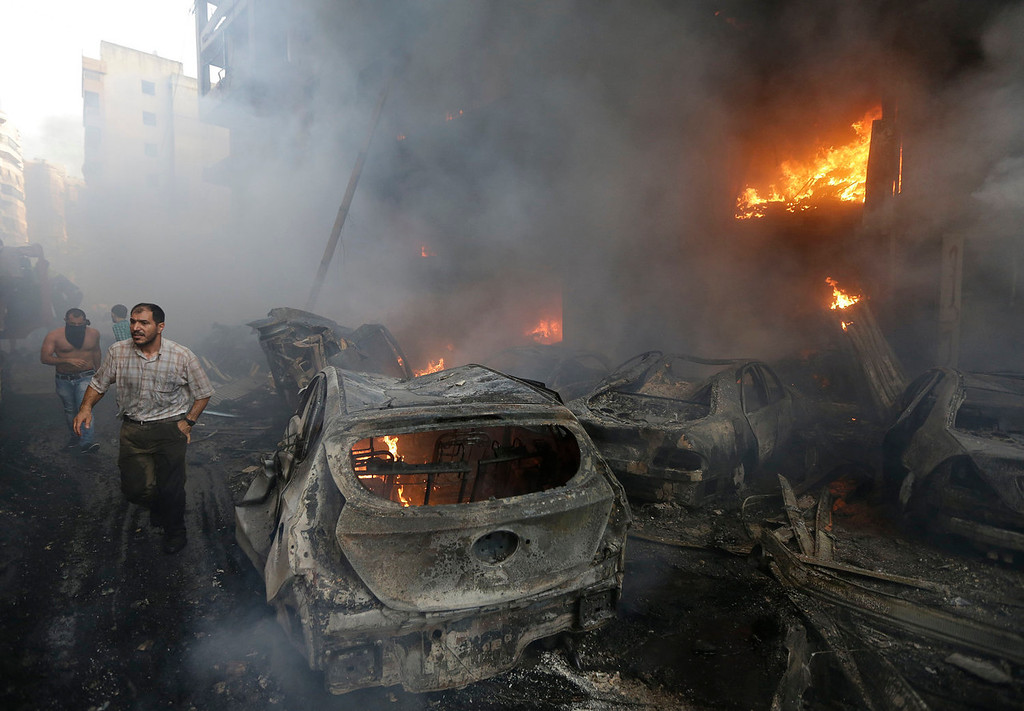 . Lebanese citizens run past a burned cars and shops at the site of a car bomb explosion in southern Beirut, Lebanon, Thursday Aug. 15, 2013. The powerful car bomb ripped through a southern Beirut neighborhood that is a stronghold of the militant group Hezbollah on Thursday, killing at least three people and trapping others in burning buildings, the media said. (AP Photo/Hussein Malla)