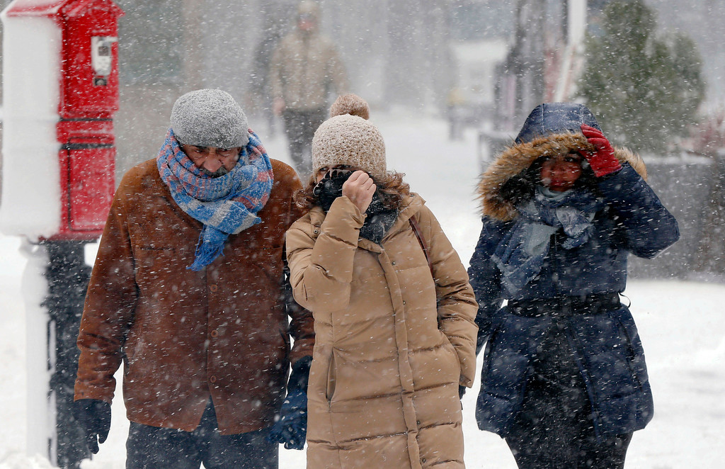 . Pedestrians make their way through blowing snow during a snowstorm, Tuesday, March 13, 2018, in Boston. (AP Photo/Michael Dwyer)