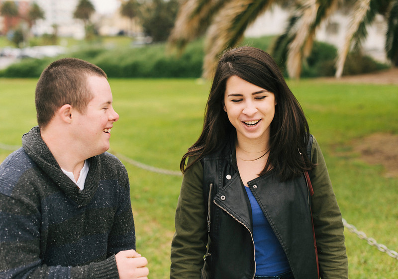 Teenage boy with Down Syndrome laughing with a Young Woman of Twenty.