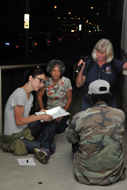 . 7/23/13 - L-R Heather Blackmun, Nancy Wilcox, and Patti LaPlace, mental health coordinator for Long Beach City interview a homeless man along Atlantic Boulevard before dawn on Tuesday.  Members of PATH People Assisting The Homeless, MHA Mental Health of America, along with city employees and volunteers join forces for three days to interview and identify the most vulnerable of the homeless in the city and attempt to help them get resources and housing. The canvasing teams have homeless people answer a 6 page survey and take their photo for a database that will improve future outreach and services. Photo by Brittany Murray / Staff Photographer