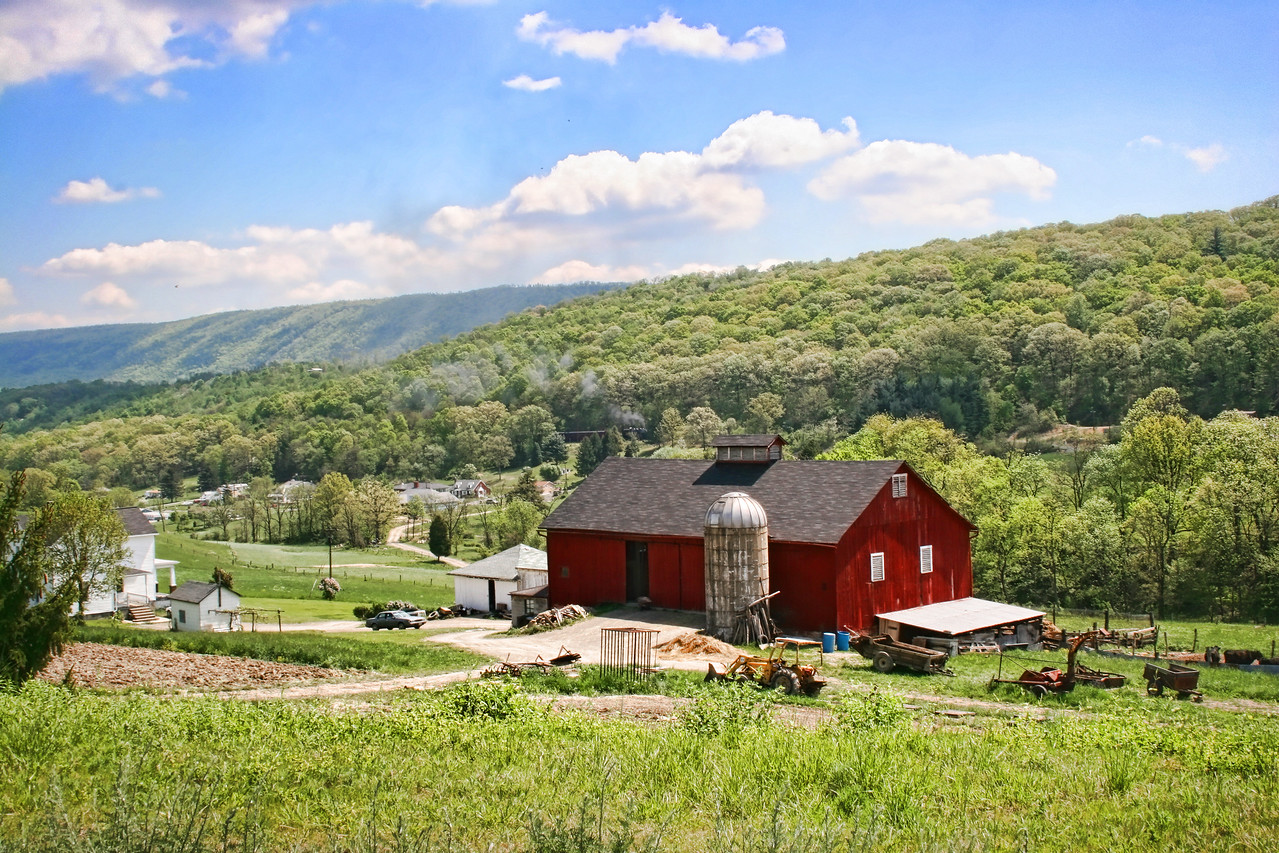 The original John Helmstetter barn with a steam train approaching in the distance. Western Maryland Scenic Railroad