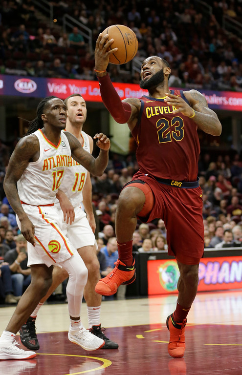. Cleveland Cavaliers\' LeBron James, right, shoots over Atlanta Hawks\' Taurean Prince in the second half of an NBA basketball game, Tuesday, Dec. 12, 2017, in Cleveland. (AP Photo/Tony Dejak)