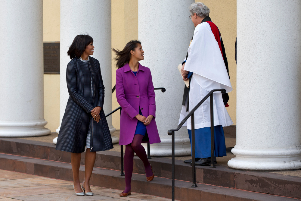 Description of . First lady Michelle Obama and daughter Malia say goodbye to Rev. Luis Leon as they leave St. John's Church in Washington, Monday, Jan. 21, 2013, after a church service during the 57th Presidential Inauguration. (AP Photo/Jacquelyn Martin)