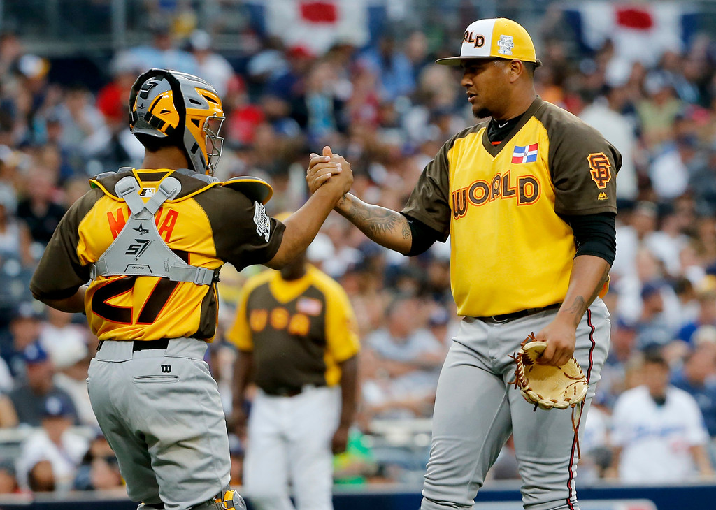 . World Team pitcher Adalberto Mejia, of the San Francisco Giants, and catcher Francisco Mejia (27) celebrate their 11-3 win against the U.S. Team after the All-Star Futures baseball game, Sunday, July 10, 2016, in San Diego. (AP Photo/Lenny Ignelzi)