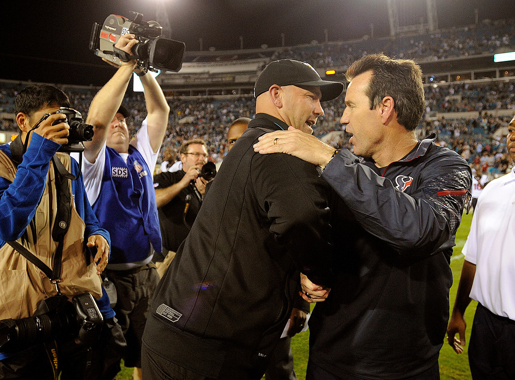 . Jacksonville Jaguars head coach Gus Bradley, left, shakes hands with Houston Texans head coach Gary Kubiak, right, after an NFL football game, Thursday, Dec. 5, 2013, in Jacksonville, Fla. Jacksonville beat Houston 27-20. (AP Photo/Stephen Morton)