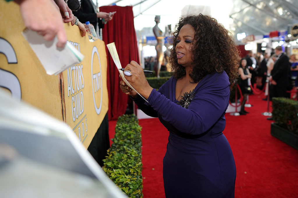 . Oprah Winfrey signs autographs on the red carpet at the 20th Annual Screen Actors Guild Awards  at the Shrine Auditorium in Los Angeles, California on Saturday January 18, 2014 (Photo by Hans Gutknecht / Los Angeles Daily News)