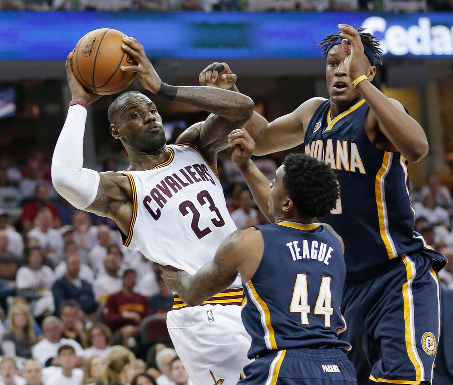 . Cleveland Cavaliers\' LeBron James, left, passes against Indiana Pacers\' Myles Turner, back, and Jeff Teague in the first half in Game 1 of a first-round NBA basketball playoff series, Saturday, April 15, 2017, in Cleveland. The Cavaliers won 109-108. (AP Photo/Tony Dejak)