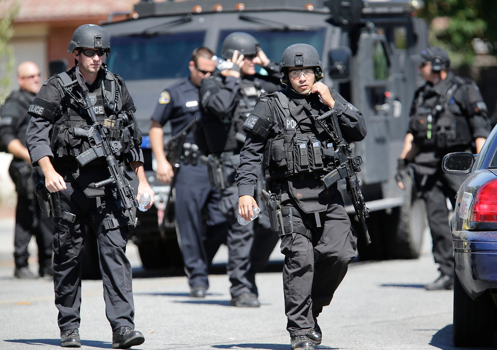 . Members of the San Jose Police Depart MERGE return to a command post after apprehending a suspect who tried to rob a check-cashing store in East San Jose, Calif. on Thursday, Aug. 1, 2013. The police were still searching for the weapon.  (Gary Reyes/Bay Area News Group)