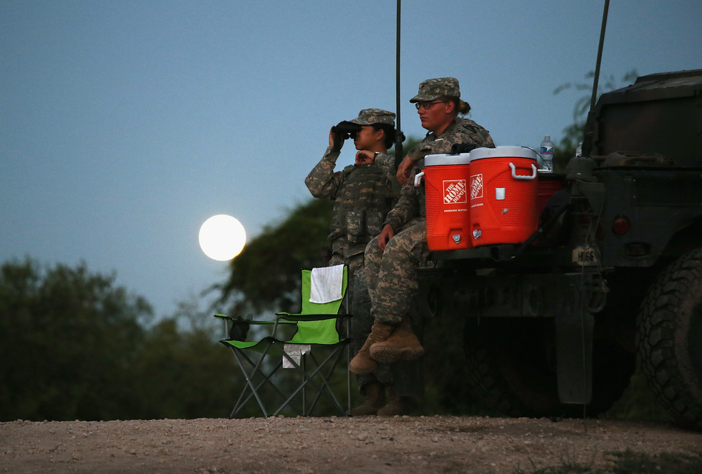 . Texas National Guard troops watch for illegal immigrant crossings as a full moon rises near the Rio Grande River at the U.S.-Mexico border on September 8, 2014 near McAllen, Texas. (Photo by John Moore/Getty Images)