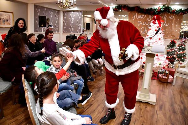 12/18/2018 Mike Orazzi | Staff Santa greet children during The Annual Forestville Carol Sing inside Nuchie's Restaurant on Tuesday night.