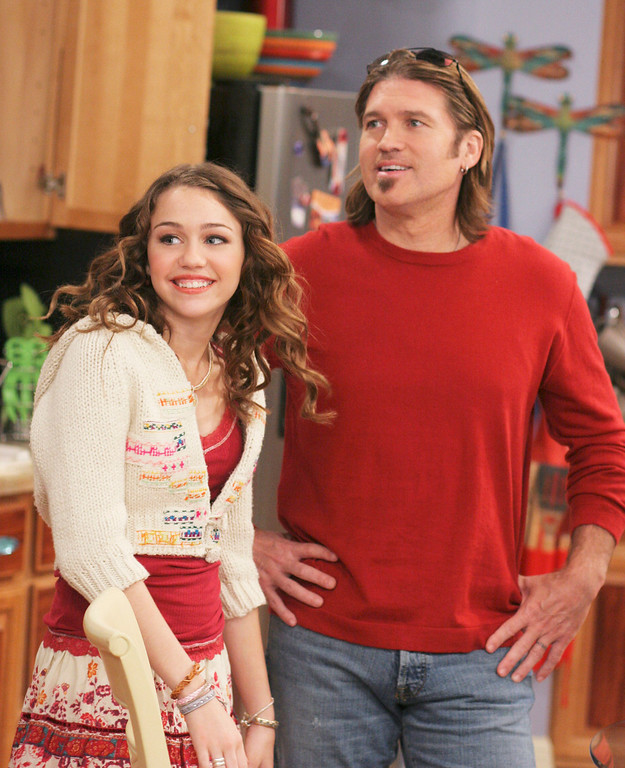 """. This undated photo released by the Disney Channel shows Miley Cyrus, left, and her father country music singer Billy Ray Cyrus in a scene from \""""Hannah Montana.\""""  Cyrus, 44, will perform Saturday, June 10, 2006, as part of the four-day CMA Music Festival.  (AP Photo/Disney Channel, Michael Ansell)"""