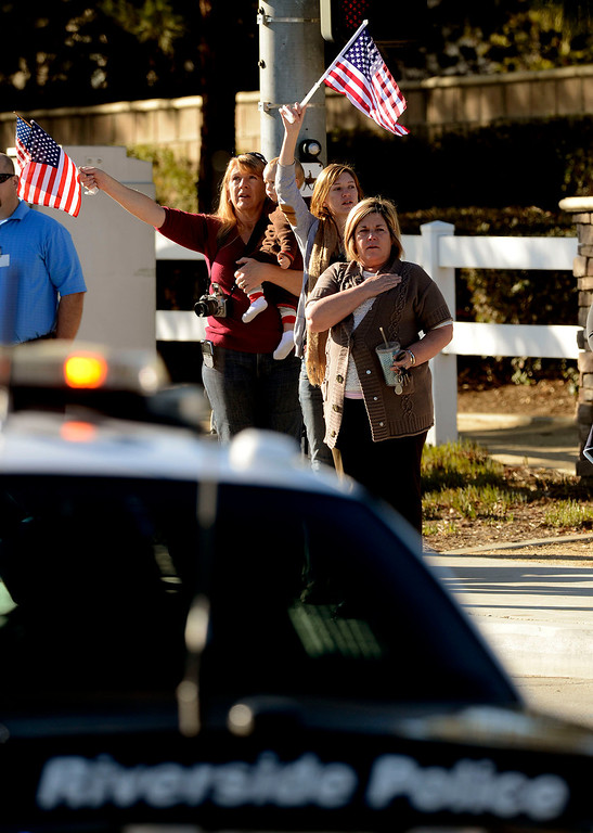 . Sara Amend, with grandson Lochlain, Laura Amend, and Sharon Kerns salute a police procession for Riverside Police Officer Michael Crain along Trautwein Road in Riverside February 13, 2013.  Crain was shot and killed last week by fugitive Christopher Dorner in Riverside.  GABRIEL LUIS ACOSTA/STAFF PHOTOGRAPHER.