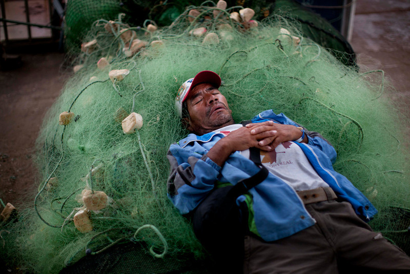 . A small scale fishermen naps on a jumble of fishing nets in Lima, Peru, Wednesday, April 2, 2014. Chilean authorities discovered surprisingly light damage Wednesday from a magnitude-8.2 quake that struck in the Pacific Ocean, Tuesday evening, near the mining port of Iquique, about 87 miles from the Peruvian border. Tsunami warnings issued for Chile, Peru and Ecuador have been lifted. Six deaths have been reported. (AP Photo/Rodrigo Abd)