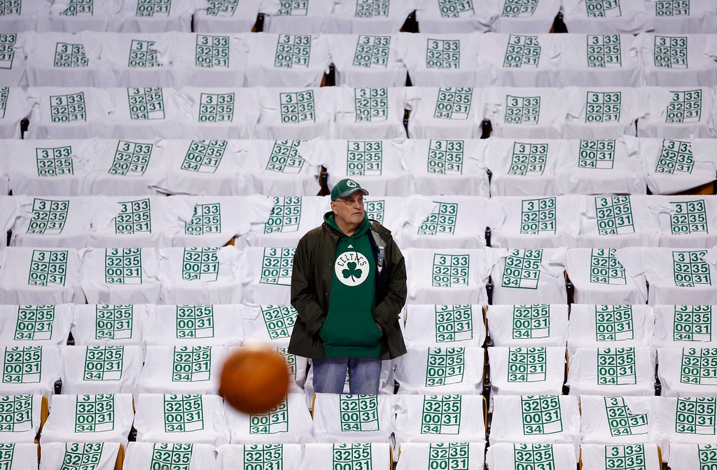 . A fan watches warm ups amid seats draped with t-shirts with retired Boston Celtics jersey numbers before an NBA basketball game against the Cleveland Cavaliers in Boston, Sunday, Feb. 11, 2018. The Celtics will retire Paul Pierce\'s number 34 following the game. (AP Photo/Michael Dwyer)