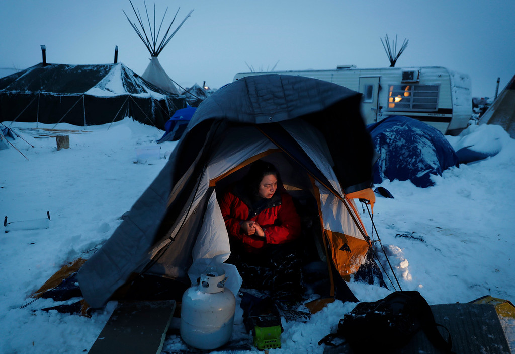 """. Karl McCartney, an Arrow Lakes Okanogan Native American from Omak, Wash., cleans snow out from his tent after a storm blew through the Oceti Sakowin camp where people have gathered to protest the Dakota Access oil pipeline in Cannon Ball, N.D., Monday, Dec. 5, 2016. Industry leaders are urging President-elect Donald Trump to make approval of the disputed Dakota Access oil pipeline a \""""top priority\"""" when he takes office next month, while opponents who have protested the project for months are vowing to stay put on their sprawling North Dakota encampment despite harsh winter weather and a tribal leaders\' call to leave. (AP Photo/David Goldman)"""