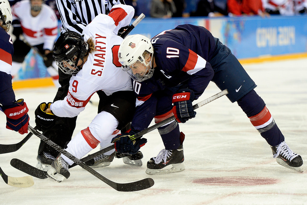 . Meghan Duggan (10) of the U.S.A. and Stefanie Marty (9) of the Switzerland battle for the puck during the first period of action at the Shayba Arena. Sochi 2014 Winter Olympics on Monday, February 10, 2014. (Photo by AAron Ontiveroz/The Denver Post)