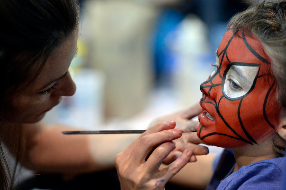 . Camdyn Nelson 5-years-old gets her face painted by Lisa Lykins of Entertainment, ect. at Denver Comic Con June 2, 2013 at the Colorado Convention Center. Camdyn chose her favorite character Spiderman. (Photo By John Leyba/The Denver Post)