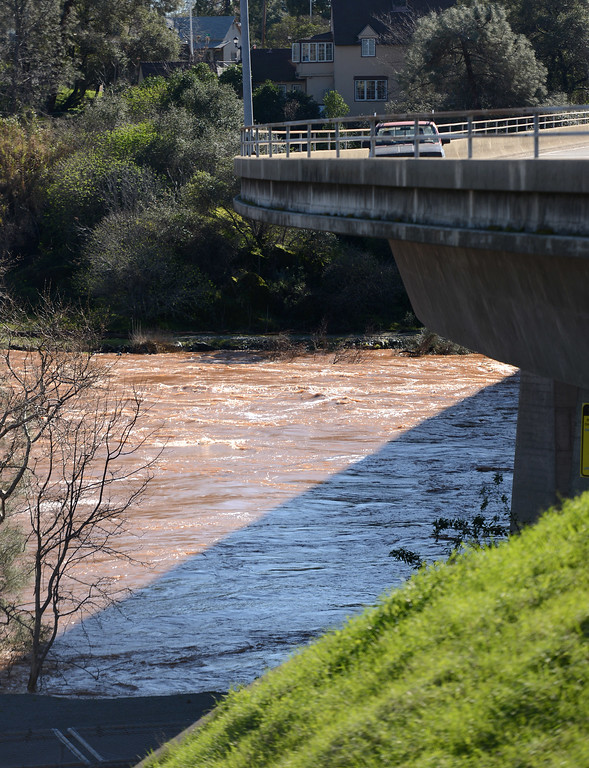 . Cars drive on the Table Mountain Boulevard bridge over a muddy Feather River as water flows over the emergency spillway Saturday, Feb. 11, 2017, and in the main spillway in Oroville, California. (Dan Reidel -- Enterprise-Record)