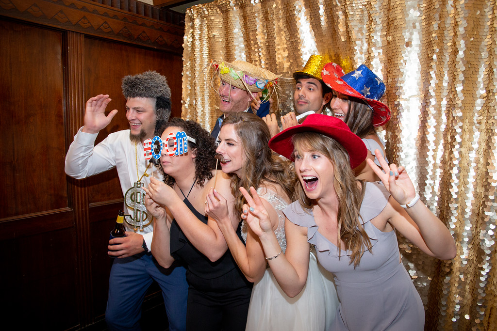 group of wedding guests taking a photo in a photo booth with a gold sequen backdrop