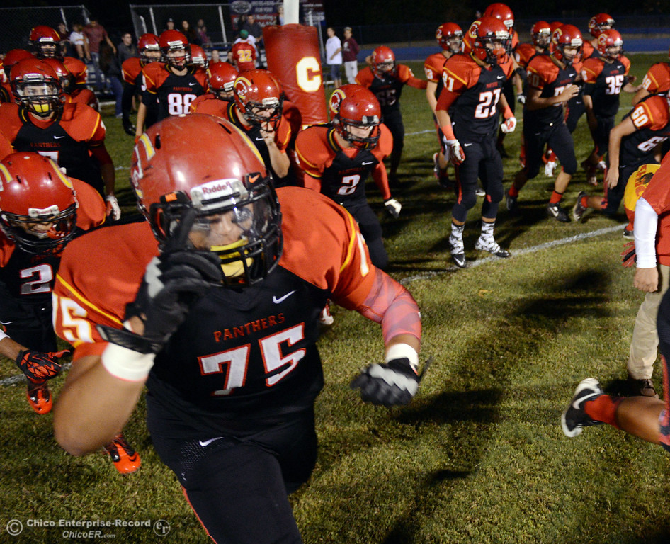 . Chico High #75  Raja Nijim (left) walks onto the field with his team against Central Valley High before the first quarter of their football game at Asgard Yard Friday, September 27, 2013, in Chico, Calif.  (Jason Halley/Chico Enterprise-Record)
